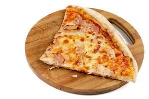 Ein gevierteltes Pizzastück mit Schinken auf rundem Holzteller vor weißem Hinterrgund