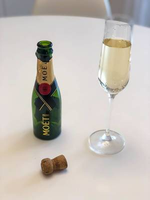 Ein Glas Champagner neben einer leeren Flaschen Mini Moët mit Korken auf dem Tisch