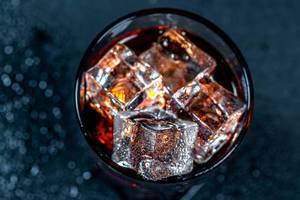 Ein Glas Cola mit Eiswürfeln in einem Gas in der Aufsicht auf schwarzem Hintergrund