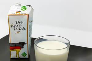 Ein Glas faire Deutsche Vollmilch - Ohne Gentechnik  - Nahaufnahme - mit Verpackung auf schwarzem Teller