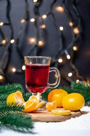 Ein Glas Glühwein mit Mandarinen auf einem Brett im Schnee mit Tannenzweigen