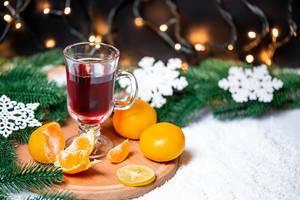 Ein Glas Glühwein mit Mandarinen und Tannenzweigen im Schnee