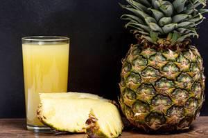 Ein Glas mit frischem Ananas Saft neben einer reifen Ananas in der Nahaufnahme