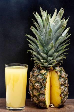 Ein Glas mit frischem Ananas Saft neben einer reifen Ananas