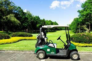 Ein Golfkart steht vor einem Golfplatz