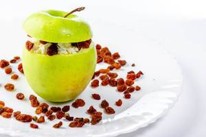 Ein grüner Apfel, gefüllt mit Hüttenkäse und Rosinen als gesunder Nachtisch