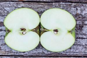 Ein grüner halbierter Apfel auf einem Tisch - Aufsicht auf den Kern