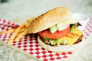 Ein halb geöffneter Cheeseburger mit Pommes im Hintergrund auf kariertem Papier