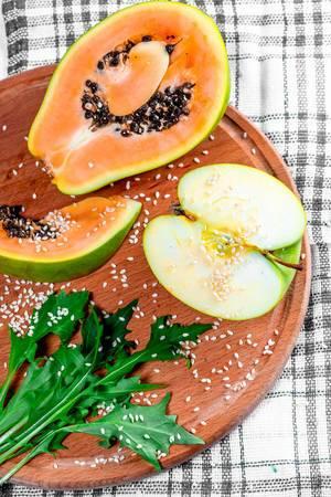 Ein halber Apfel und Papaya-Scheiben mit Ruccola und Sesam bestreut, auf einem runden Holzbrettchen
