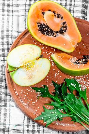 Ein halbes Apple ein Stück Papaya-Rucola und Sesam auf einem Holzbrett