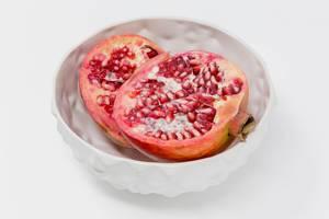 Ein halbierter Granatapfel in weißer Schale auf weißem Hintergrund
