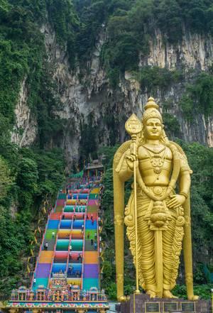 Ein Hindu-Temple mit einer riesigen goldenen Statue bei den Batu Höhlen in Kuala Lumpur