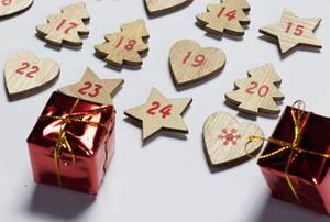 Ein hölzener Adventskalender mit kleinen Weihnachtsgeschenken auf weißem Hintergrund