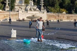 Ein junger Mann macht eine Show mit Seifenblasen auf dem Piazza del Popolo in Rom
