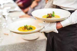 Ein Kellner trägt Teller mit Kürbis-Suppe und Lachs in einem Restaurant