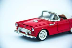 Ein Klassisches rotes Cabrio Modellauto auf weißem Hintergrund