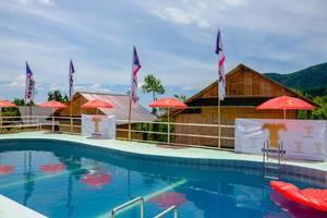 Ein kleiner Swimmingpool mit roten Sonnenschirmen in Kampo Hiyang