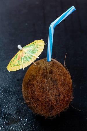 Ein Kokosnuss-Cocktail mit Schirm und Strohhalm