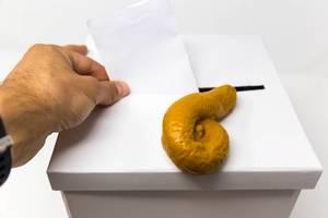 Ein Kothaufen / Scheisshaufen liegt auf einer Wahlurne, während ein Mann seinen Stimmzettel abgibt