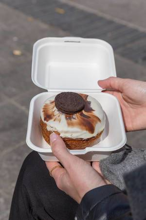 """Ein Kronut-Donut aus Blätterteig, mit weißem Schokoguss in einer weißen Burgerbox, aus dem Feinkostgeschäft """"chök"""" in Barcelona (Spanien)"""