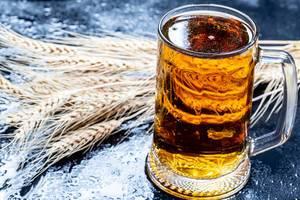Ein Krug Bier mit Weizenähren auf schwarzem Hintergrund