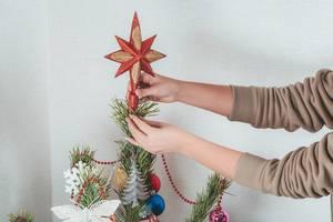 Ein Mädchen steckt den Stern auf die Weihnachtsbaumspitze