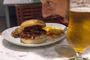Ein Mann beißt vor Heißhunger in einen Pulled-Beef Burger