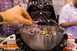 Ein Mann greift in eine Süßigkeitenschale nach Bonbons die von einer Darth Vader Figur gehalten wird