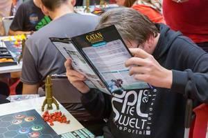 Ein Mann liest sich die Catan Sternenfahrer Spielanleitung durch