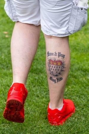 Ein Mann mit Tattoo Ming Hätz am Unterschenkel