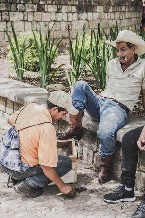 Ein Mann poliert die Schuhe eines Cowboys