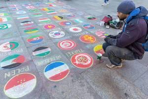 Ein Mann sammelt Spenden mit auf dem Boden des Kölner Weihnachtsmarkts gemalte Länderflaggen