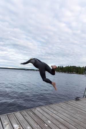 Ein Mann springt in einen See bei Padasjoki, Finnland, während er einen Taucheranzug trägt
