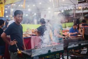 Ein Mann steht im Rauch eines Grills und grillt Fleisch am Spieß