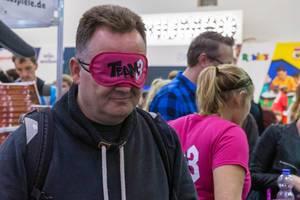 Ein Mann trägt die Team 3 Augenbinde auf der Essener Spielemesse
