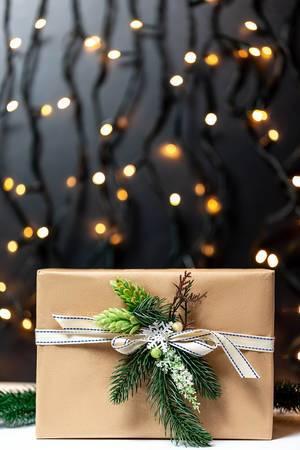 Ein mit Tannenzweigen und Zapfen verziertes Weihnachtsgeschenk in Naturpapier vor beleuchtetem Hintergrund