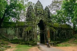 Ein Motorrad fährt durch das Victory Gate beim Angkor Thom in Siem Reap