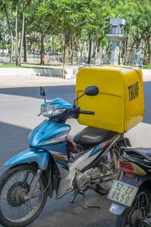 Ein Motorroller mit einer gelben Trump-Kiste in Saigon