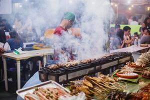 Ein Phillippinese grillt Spieße mit Fleisch auf einem Markt