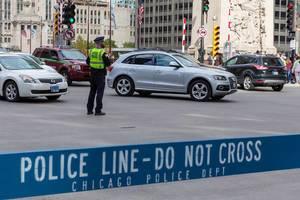 """Ein Polizist steht mitten im Straßenverkehr in Downtown Chicago, während ein Bereich ist von einer blauen Barriere mit dem Schriftzug """"Police line - Do not cross"""" abgesperrt"""