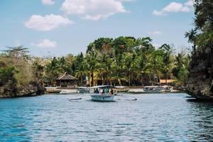 Ein Pumpenboot fährt Touristen über das Meer vor der Insel