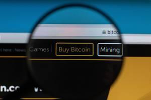 """Ein """"Kaufe Bitcoin"""" Button unter einer Lupe"""