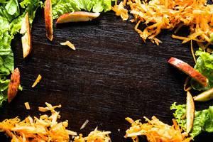 Ein Rahmen aus gehacktem Salat, geriebenen Karotten und geschnittenem Apfel auf hölzernem Hintergrund