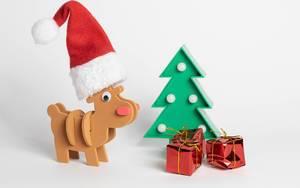 Ein Rentier mit Weihnachtsmütze und einem Weinachtbaum mit roten Geschenken auf weißem Hintergrund