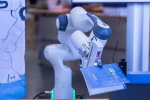 Ein Roboter hält eine Agenda des Bits & Pretzels Festivals