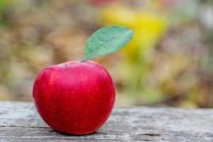 Ein roter Apfel mit Blatt auf einem Holztisch - Nahaufnahme