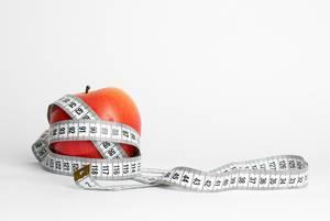 Ein roter Apfel mit einem Maßband auf weißem Hintergrund