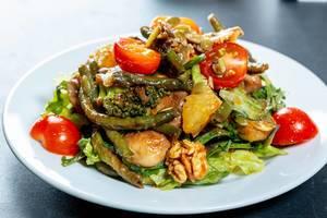 Ein Salat aus frischem Gemüse mit Pilzen, Walnüssen und Kirschtomaten