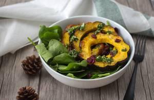 Ein Salat aus Speisekürbis mit Spinat und Cranberries in einer Schüssel