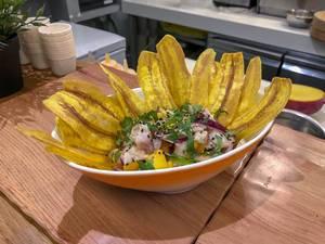 Ein Salat mit roten Zwiebeln und Ananasstücken mit Scheiben frittierter Bananen in einer Schüssel